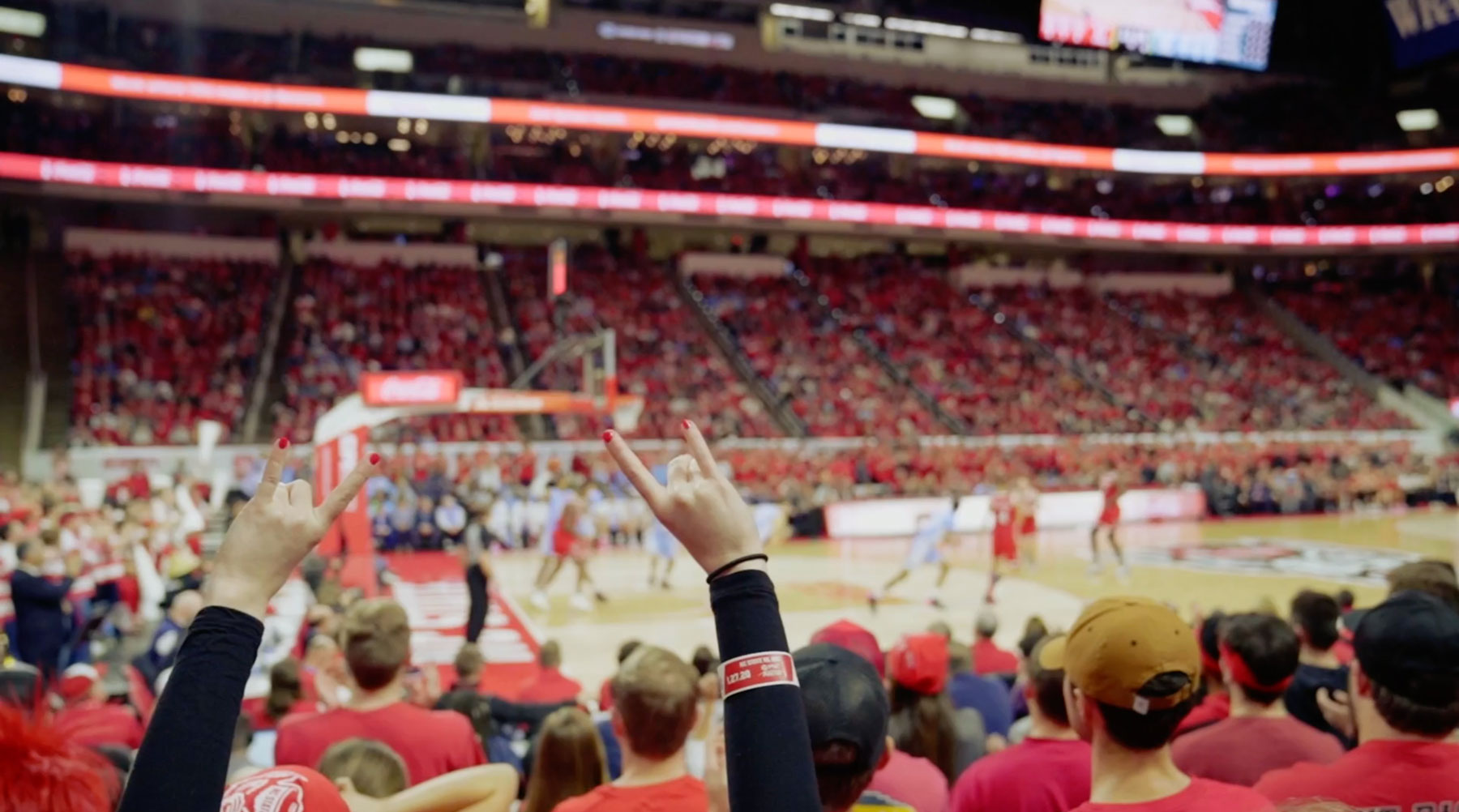 Fan at N.C. State basketball game with Wolfpack hand gesture