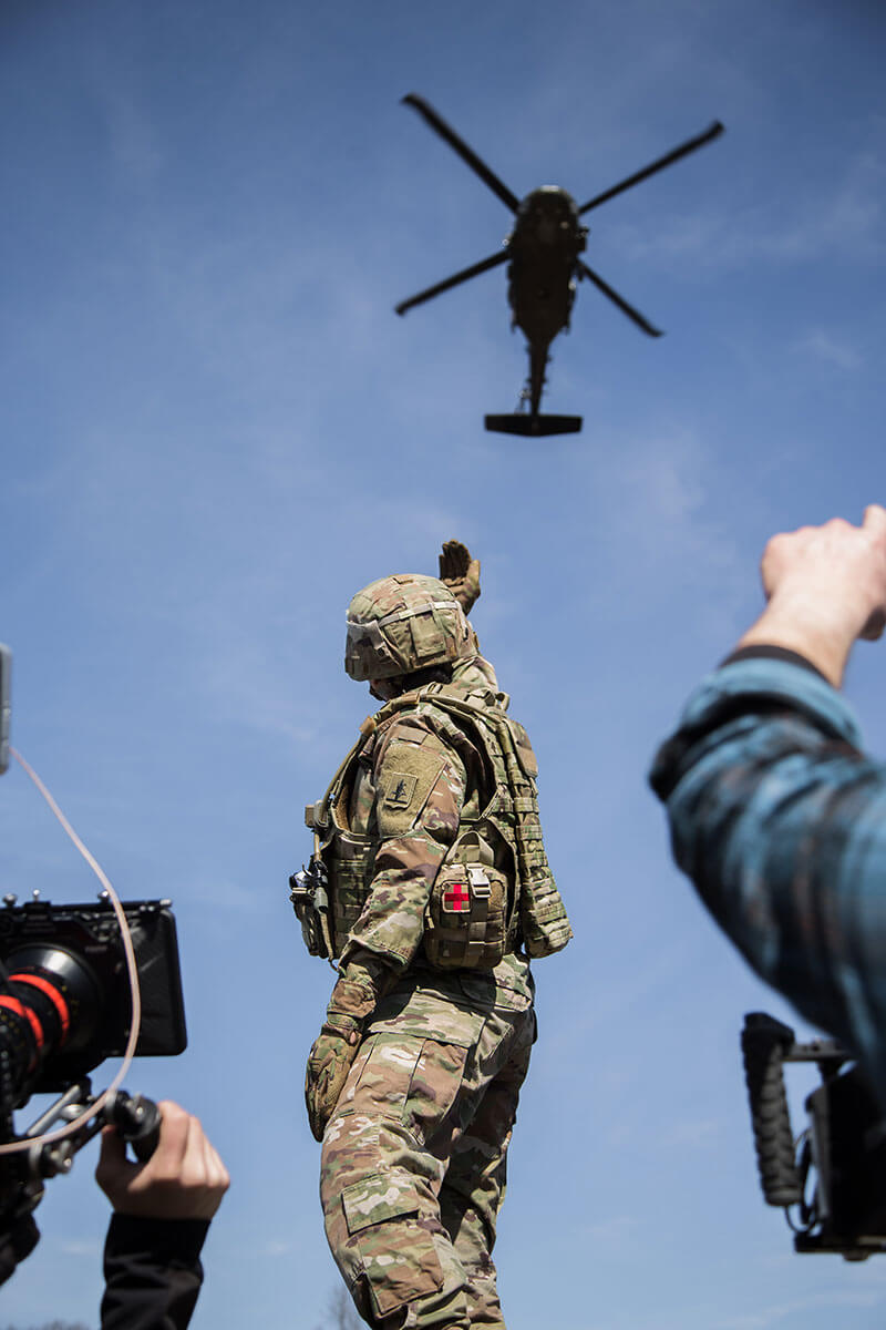 Behind the scenes of an Army National Guard video shoot with a soldier and helicopter