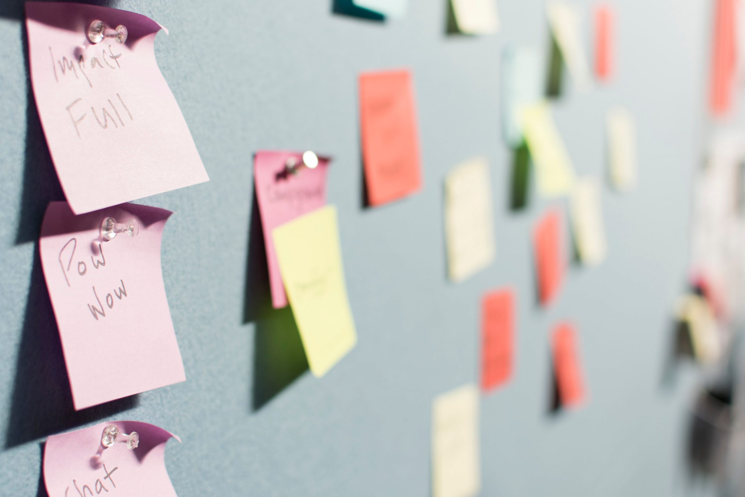 image of colorful post-it notes pinned on a bulletin board
